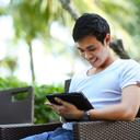 man in white shirt using tablet computer outdoors
