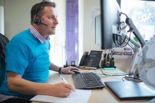 IT Services staff member using softphone and looking at comoputer screen