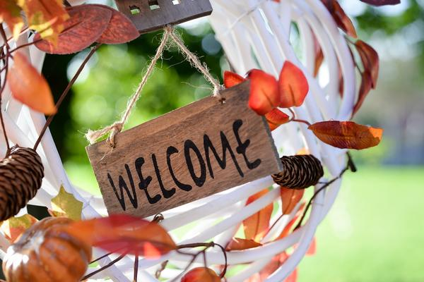 A white wreath with autumn leaves tucked in and a small sign in the centre saying 'welcome'