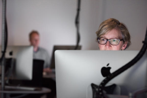 Woman on computer, with shadowy man in background