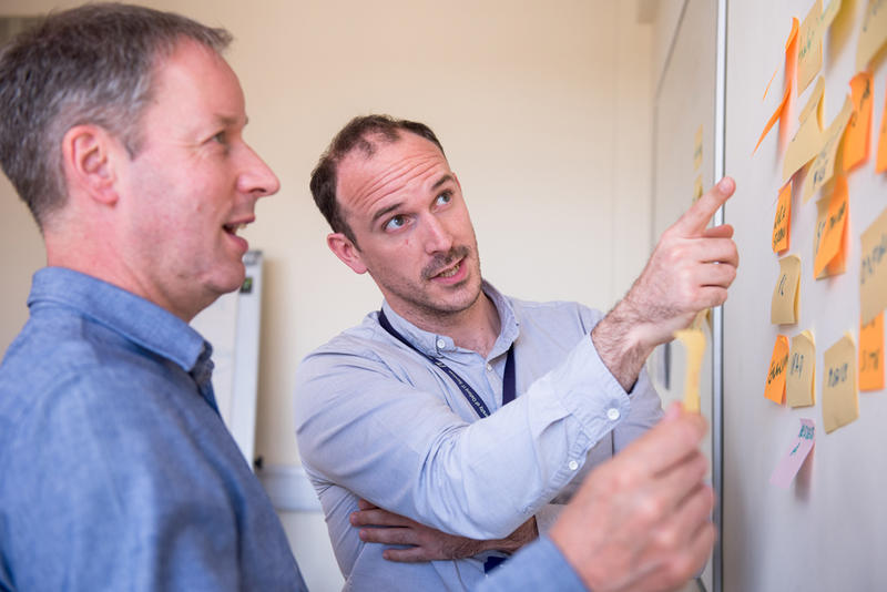 Two men looking at a whiteboard covered in post-it notes.